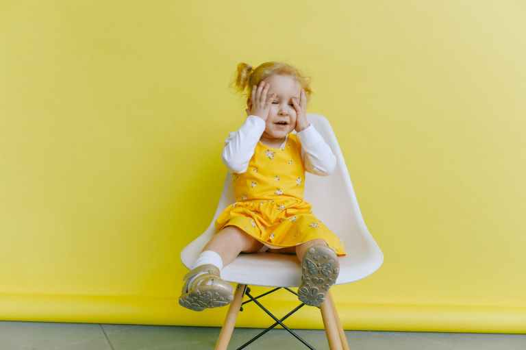 girl in yellow dress covering her face with her hands